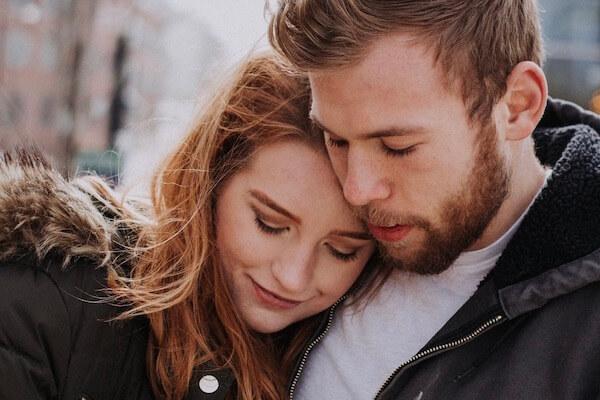 Eine Frau lehnt ihren Kopf an die Schulter ihres Partners. Gemeinsam wollen sie ihre Beziehungsprobleme mit einem Coaching klären.