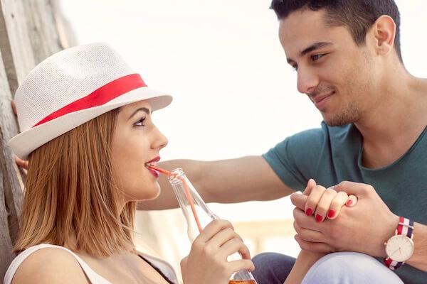 Ein junges Paar flirtet am Strand durch Blickkontakt, Händchen halten und schüchternem Lächeln.