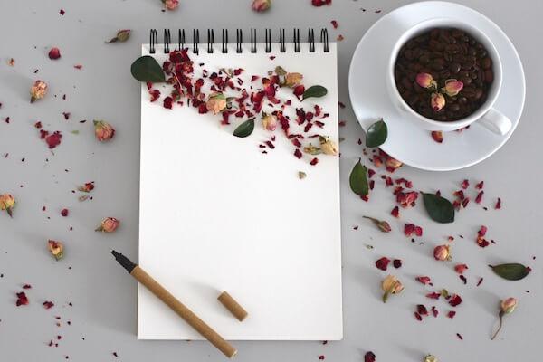 Mit einem Schreibblock, einer Tasse Kaffee und Rosenblätter über den Tisch in einen Workshop über die Liebe starten.