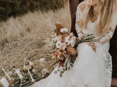 Eine Frau sitzt im Hochzeitskleid mit ihrem Brautstrauss auf einem Sessel und lächelt überglücklich.