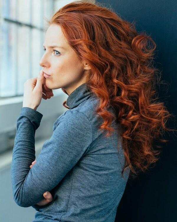 Eine nachdenkliche Frau lehnt an einer Wand und grübelt über ihre gescheiterten Beziehungen nach.