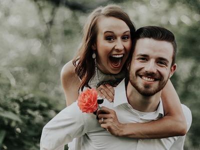 Eine Frau umarmt überglücklich ihren neuen Freund. Beide strahlen in die Kamera.