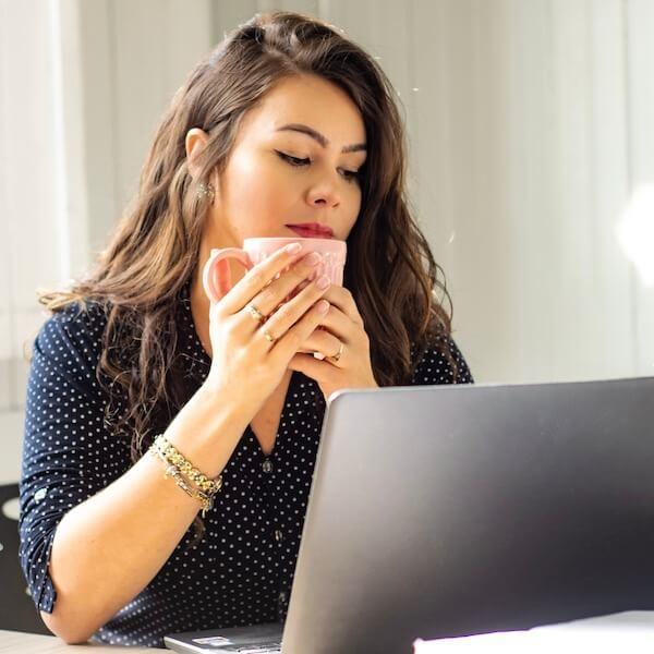 Eine junge Frau schaut enttäuscht in das Online-Datingportal auf ihrem Rechner.