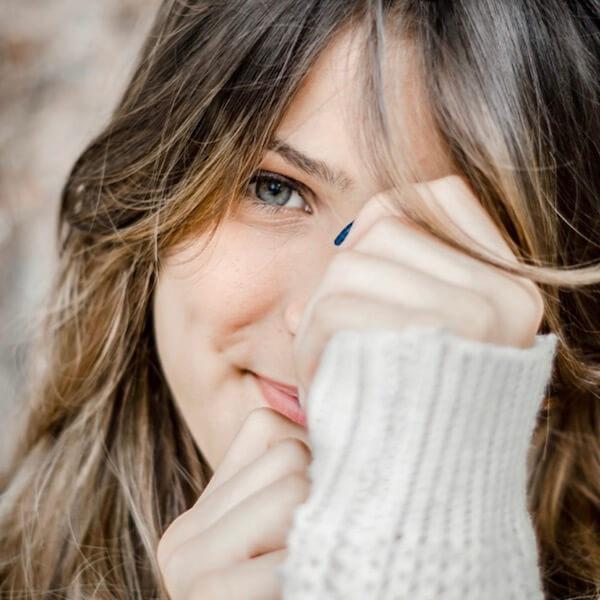 Eine schüchterne Frau versteckt sich hinter ihren Händen und lächelt verlegen.